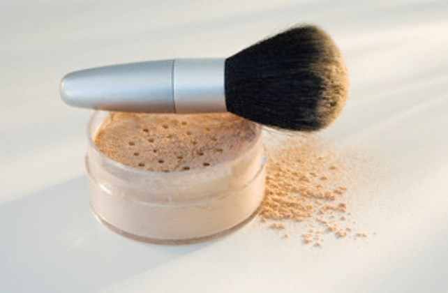 Powdered mineral makeup and brush --- Image by © Tetra Images/Corbis