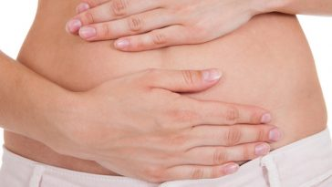 Close up of woman's hands on belly isolated on white background